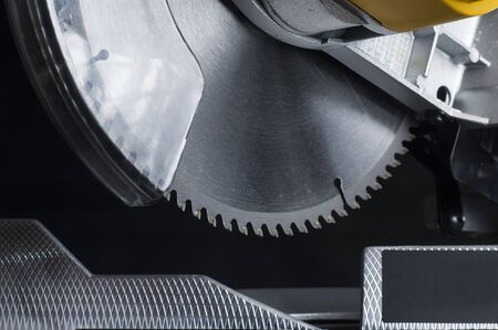 miter: miter saw. Cutting disk on black background.