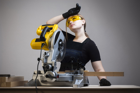 tired worker: Tired worker. Young beautiful woman in overalls and glasses with disk saw.