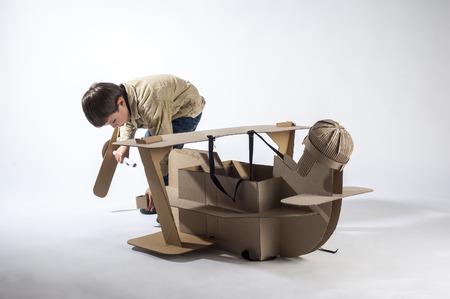 airscrew: Young aviator assembles cardboard plane. Making airscrew. Stock Photo