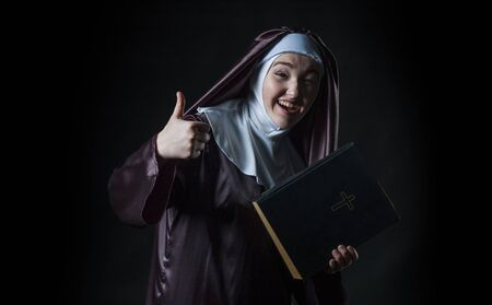 advertises: Young nun advertises bible and shows thumbs Stock Photo