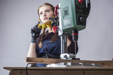 menuisier: belle femme charpentier au travail en utilisant la machine de forage vertical