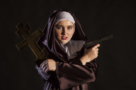 black nun: Nun holding gun in one hand and cross in another. isolated on black background.