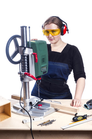 worker working: beautiful female carpenter at work using vertical drilling machine. Photo on white background.