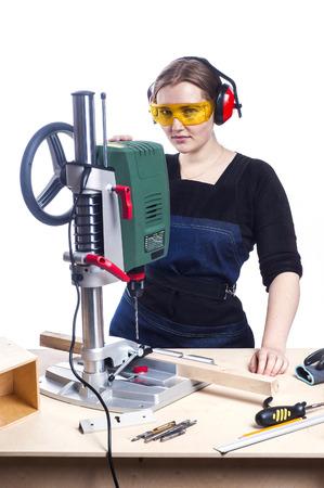 obrero trabajando: hermosa carpintero mujer en el trabajo usando la máquina de perforación vertical. Foto en el fondo blanco. Foto de archivo