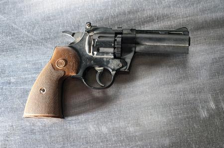 pellet gun: Photo of  black revolver on vintage metal background. Stock Photo