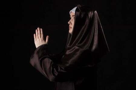 low key lighting: Young attractive nun is praying. Side view.  Photo on black background. Low key lighting.