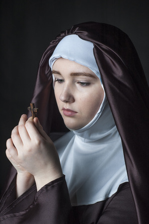 religious habit: Close up portrait of young nun. Nun is praying. Photo on black background. Stock Photo