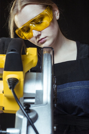 young worker: woman with a circular disk saw