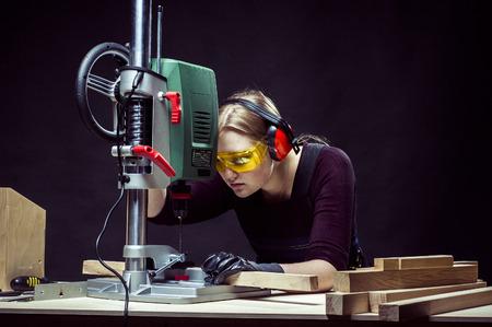 carpintero: hermosa carpintero mujer en el trabajo usando la m�quina de perforaci�n vertical. Foto en el fondo negro.