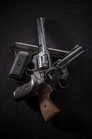 pistols: three different pistols on black background. revolvers and pistols. Stock Photo