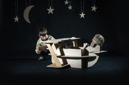 Young aviator assembling corrugated plane on the dark night sky background. Stock Photo