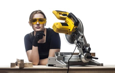 industry background: young beautiful woman in overalls and glasses with disk saw preparing for cutting. Photo on white background.