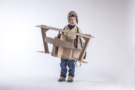 Young aviator in a homemade cardboard aircraft on white background. Boy hamming Stock Photo