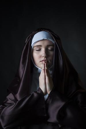 black nun: Close up portrait of young nun. Nun is praying. Photo on black background. Stock Photo