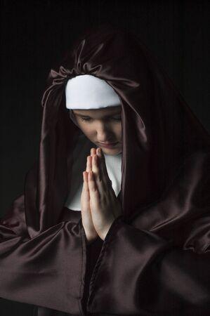 black nun: Young nun prays. Photo on black background. Low key lighting.