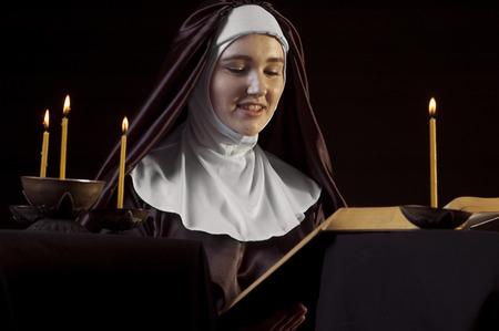 black nun: Young woman nun reading bible on black  background. Through the candles. Low-key lighting.