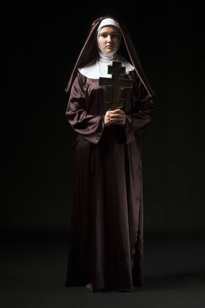 religious habit: Full growth photo of young catholic nun with orthodox cross