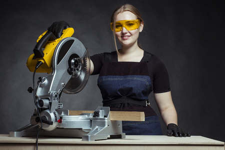 miter: young beautiful woman in overalls and glasses with disk saw preparing for cutting. Photo on black background.