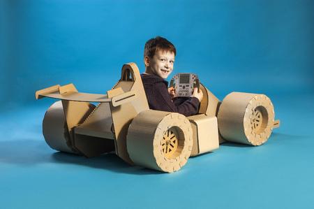 photo of  young racer on a cardboar racing car on blue background Zdjęcie Seryjne - 59615246