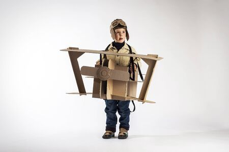 flight helmet: Smiling boy is playing with handmade cardboard plane. Photo on white background.