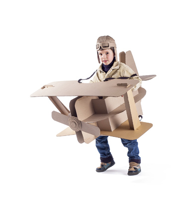 flight helmet: Young aviator in a homemade cardboard aircraft on white background. Stock Photo