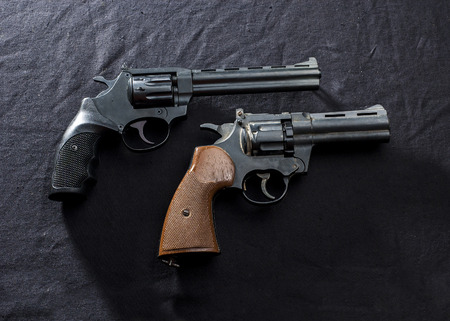 two old  revolvers on black background.