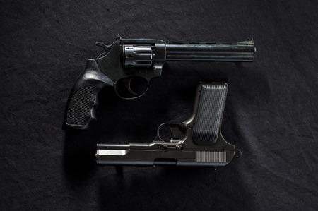 pellet gun: two old  revolvers on black background.