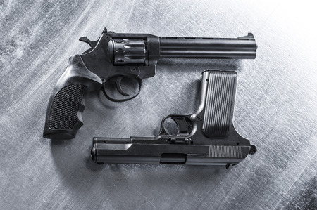 violence and trigger: semiautomatic pistol and revolver on metal background. Stock Photo