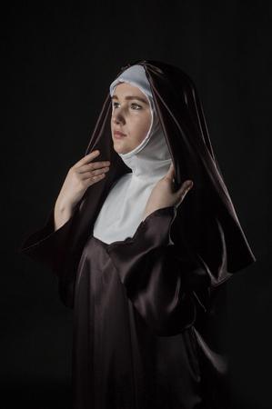 religion catolica: retrato de la joven y bella monja. iluminación de bajo perfil. En negro.
