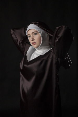 religion catolica: portrait of the young beautiful nun. Low key lighting. On black.