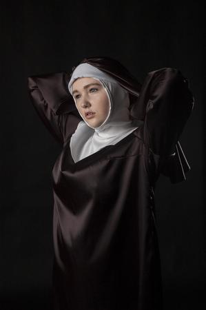 nun: portrait of the young beautiful nun. Low key lighting. On black.