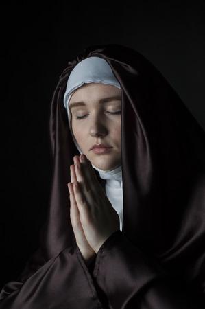 religion catolica: Monja joven ruega. Foto sobre fondo negro. Iluminación de bajo perfil.