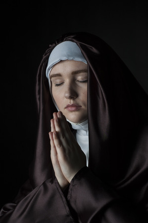 religious habit: Young nun prays. Photo on black background. Low key lighting.