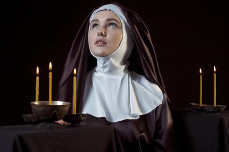 nun: Young catholic nun through the candles. Photo on black background. Low key lighting.