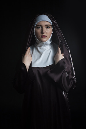 low key lighting: Front portrait of the young beautiful nun. Low key lighting. On black.