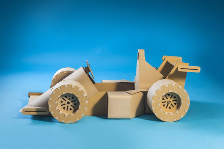 f1: Photo of cardboard racing car on blue background