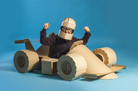 photo of  young racer in glasses on a cardboard racing car on blue background Zdjęcie Seryjne - 70936121