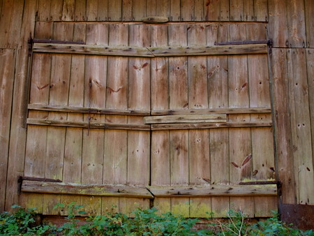 Large wooden doors of the old barn with iron canopies