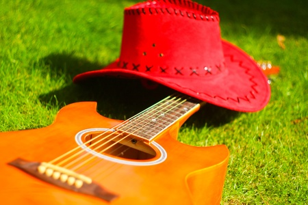 western attire: Photo with red hat and guitar on the grass Stock Photo