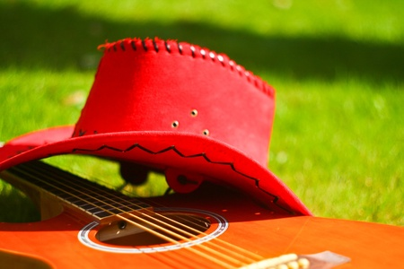 Photo with red hat and guitar on the grass photo