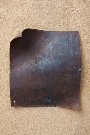 Rusty metal tag on yellow wall Stock Photo - 7560435