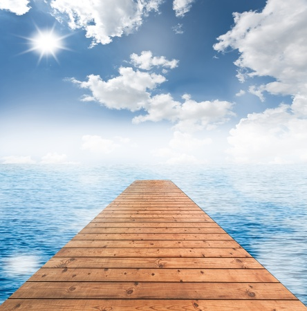 Wooden bridge with cloudy blue sky and the blue sea photo