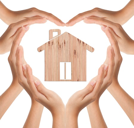 estate: Hands make heart shape with wood house