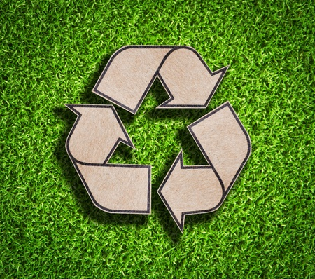 Recycle sign on green grass background Stock Photo - 9403478