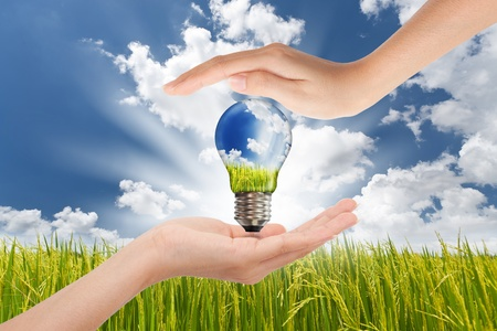 utilities: Hands saving , Global Concept of Green Energy Solutions With Light bulb and Planet on Bright Landscape Stock Photo