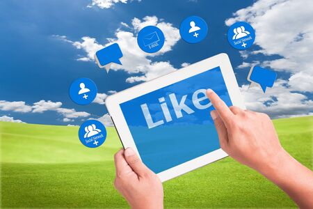 hand holding a touchpad pc and press like button with mail , add friend and comment icons Stock Photo - 9733667