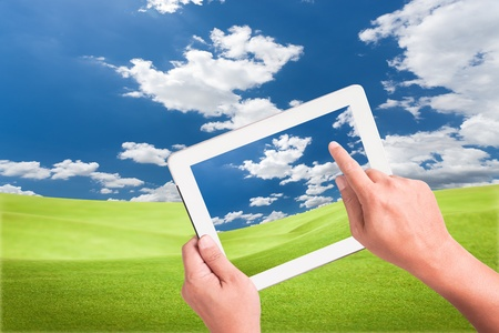 hand holding a touchpad pc with green field