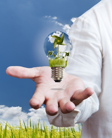 recycle tree: paddle , windmill and blue sky in light bulb on hand