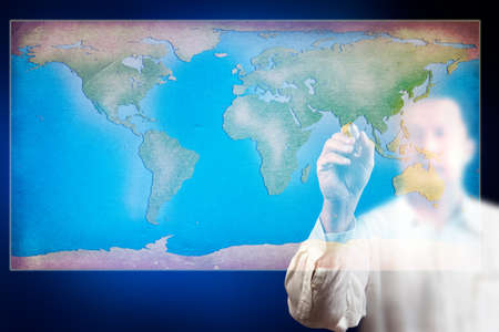 Businessman drawing a map of the world on glass photo