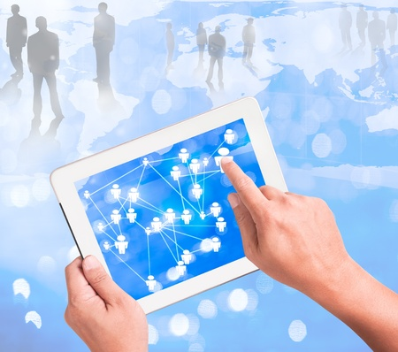 Businessman holding a touchpad pc and surfing in the social network photo